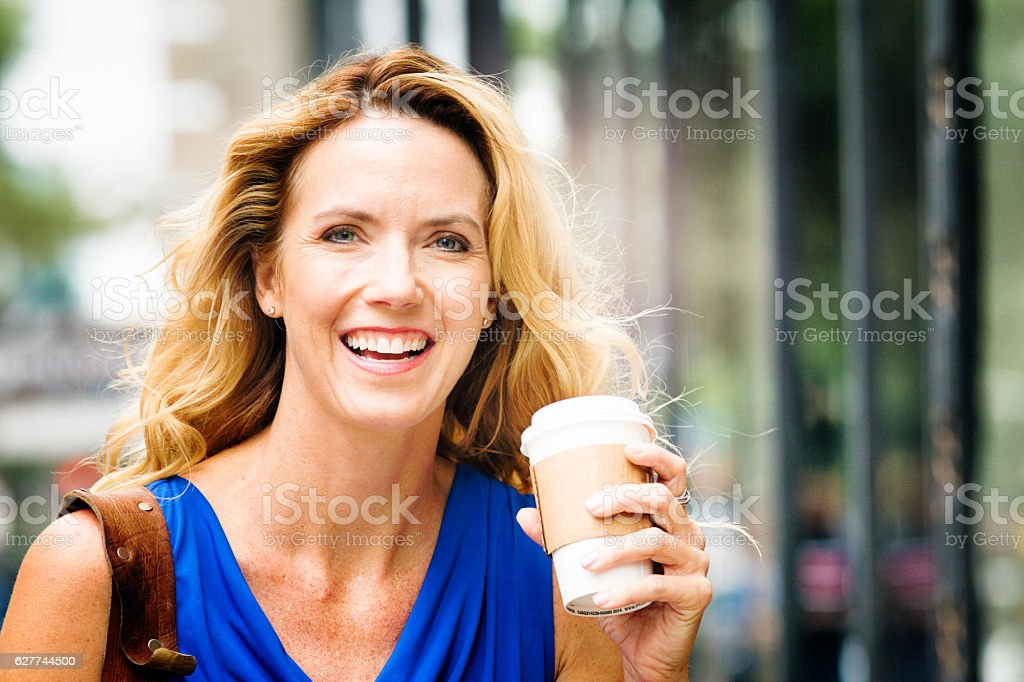 Smiling mature blonde happy American woman street portait with coffee stock photo
