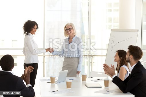 924520168 istock photo Smiling mature boss handshaking african employee congratulating with promotion 1095047048