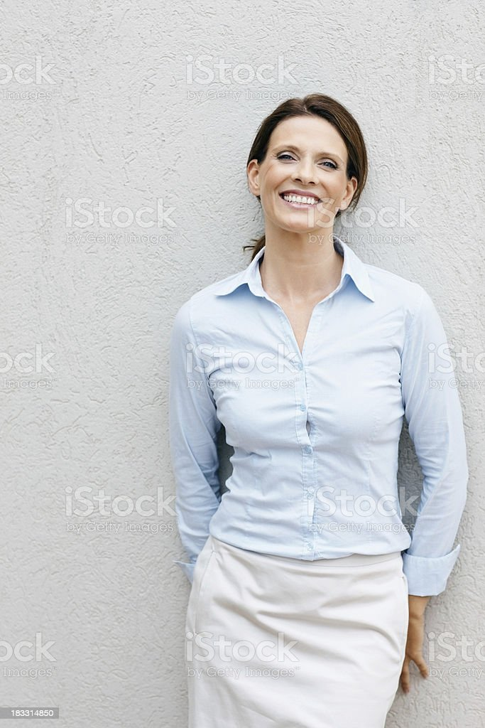 Smiling, mature business woman leaning against a wall royalty-free stock photo