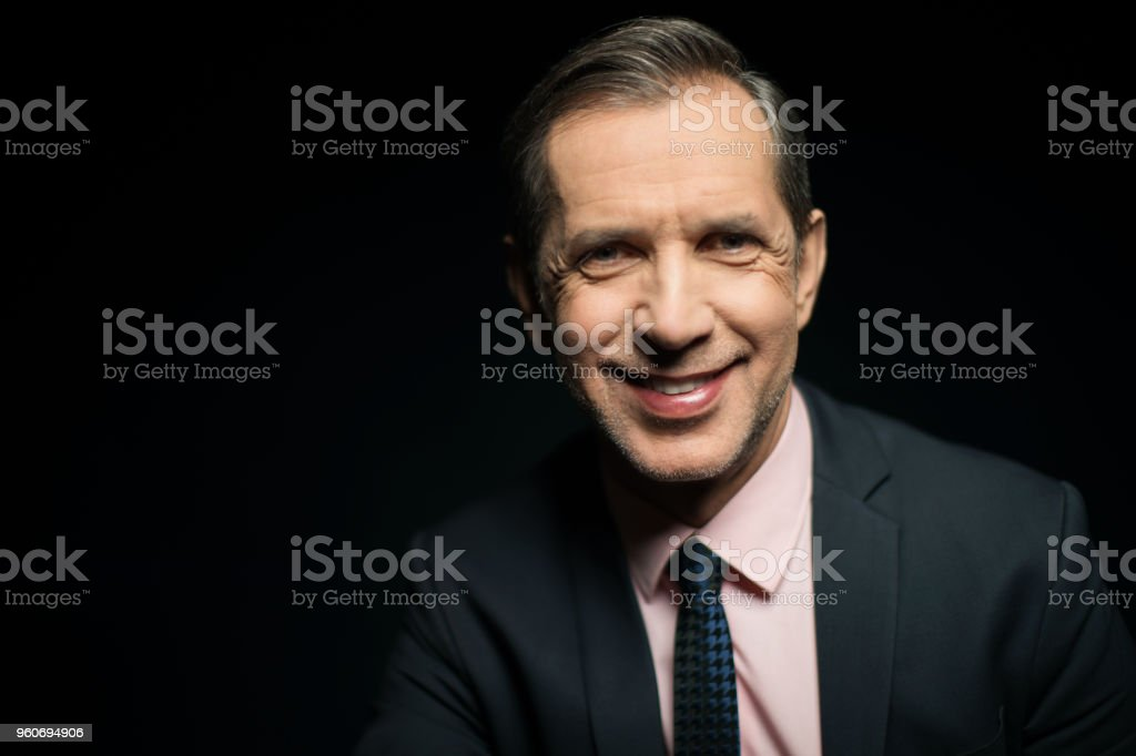 Smiling mature businessman on black background stock photo