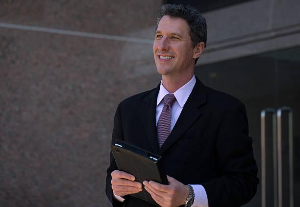 smiling mature  businessman outside an office building - foto's van business people on computer stockfoto's en -beelden