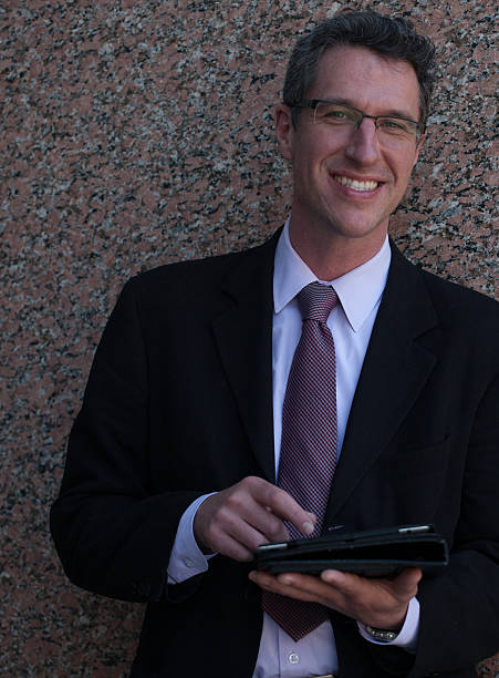 smiling mature businessman outside an office building using tablet - foto's van business people on computer stockfoto's en -beelden