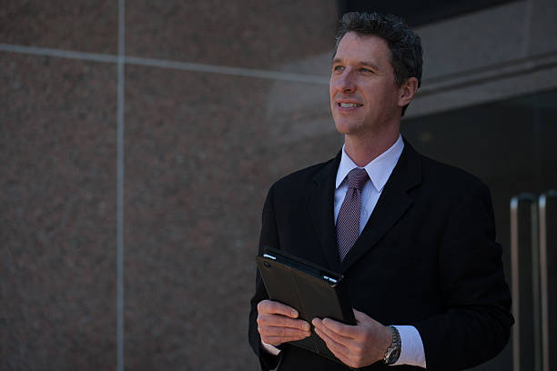 smiling mature businessman outside an office building with tablet - foto's van business people on computer stockfoto's en -beelden