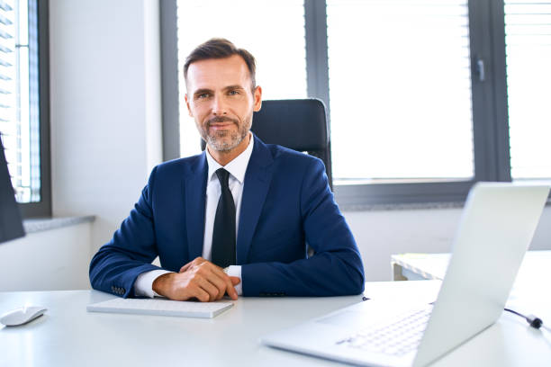Smiling mature businessman sitting at office desk looking at camera stock photo