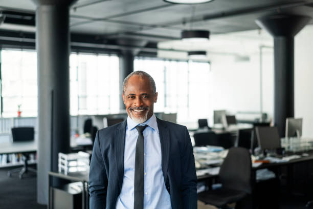 Smiling mature businessman standing in new office stock photo