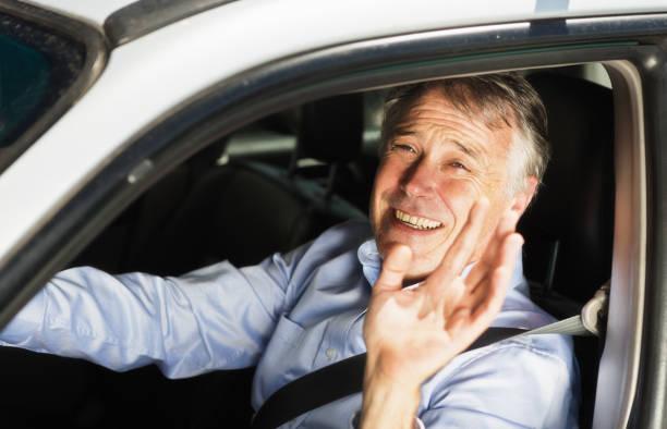 smiling mature businessman waves through car window - homme faire coucou voiture photos et images de collection
