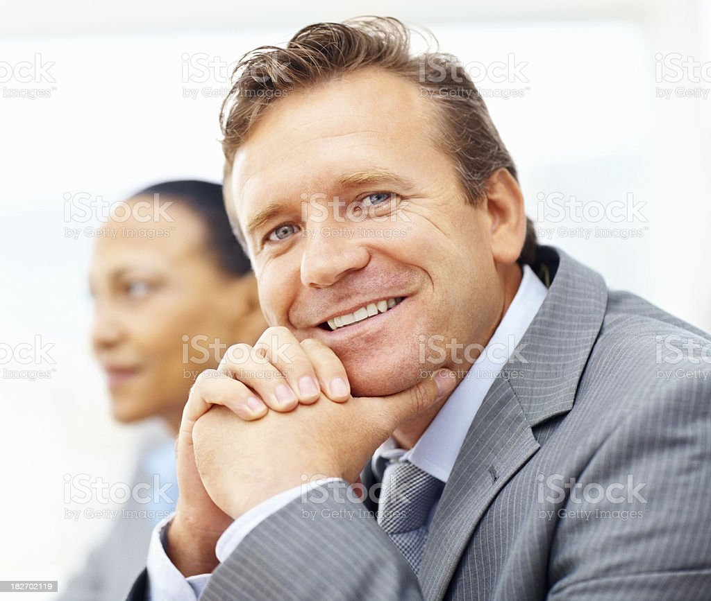 Smiling mature businessman with colleague in the background royalty-free stock photo