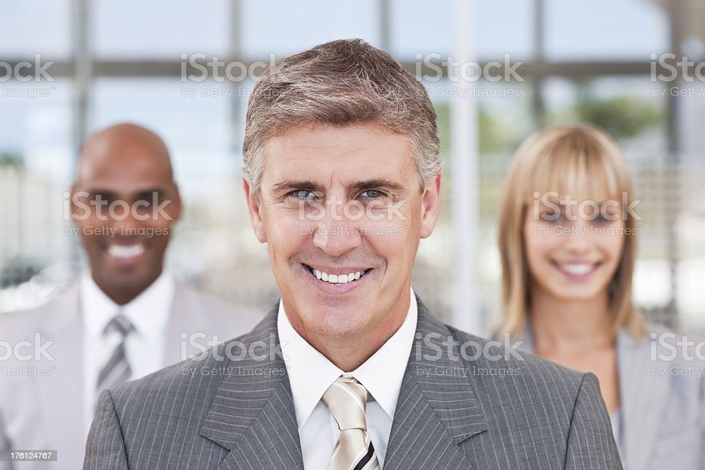 Smiling mature businessman with colleagues in the background royalty-free stock photo