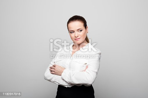 1132314350 istock photo Smiling mature businesswoman standing arms crossed 1132317015