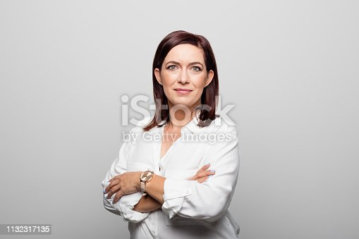 1132314350 istock photo Smiling mature businesswoman standing arms crossed 1132317135