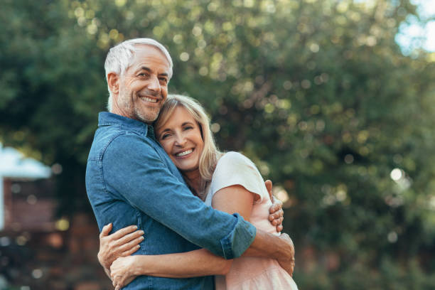 Smiling mature couple affectionatley hugging each other outside stock photo