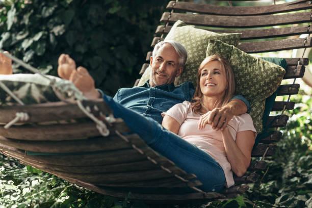 Lächelndes reifes Paar liegt zusammen in einer Hängematte draußen – Foto