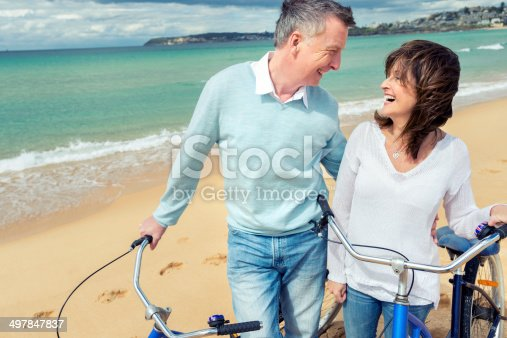 istock Smiling mature couple pushing bicycles on the beach 497847837