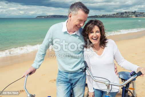 istock Smiling mature couple pushing bicycles on the beach 497847843