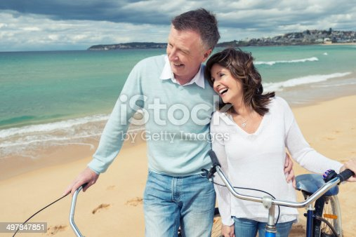 istock Smiling mature couple pushing bicycles on the beach 497847851