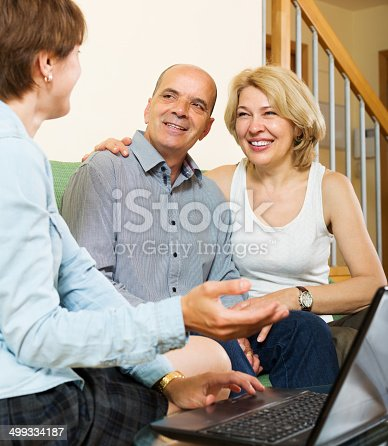584597964 istock photo Smiling mature couple questionnaire for agent or employee 499334187
