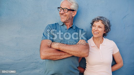 529076288 istock photo Smiling mature couple standing together and looking away 534210860