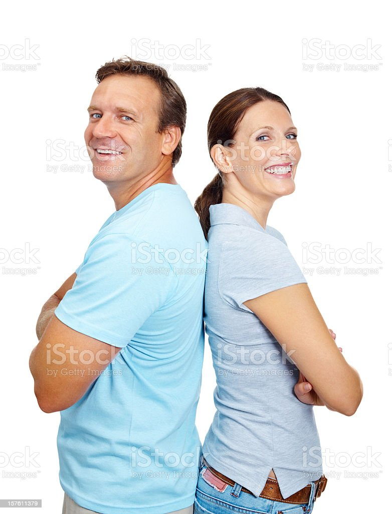 Smiling mature couple standing with arms crossed against white stock photo