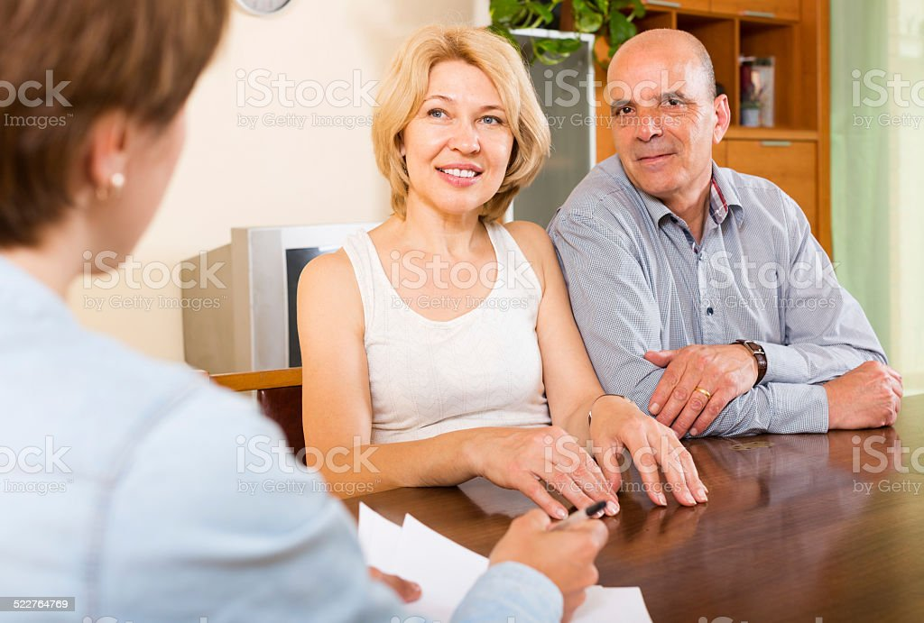 Smiling mature couple  talking with employee stock photo