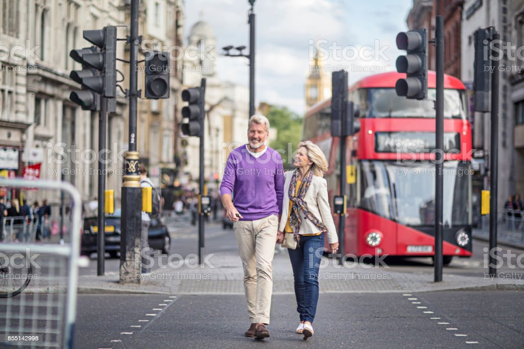 Smiling mature couple walking in the street of London stock photo