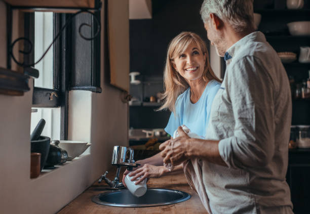 Smiling mature couple washing dishes in their kitchen stock photo