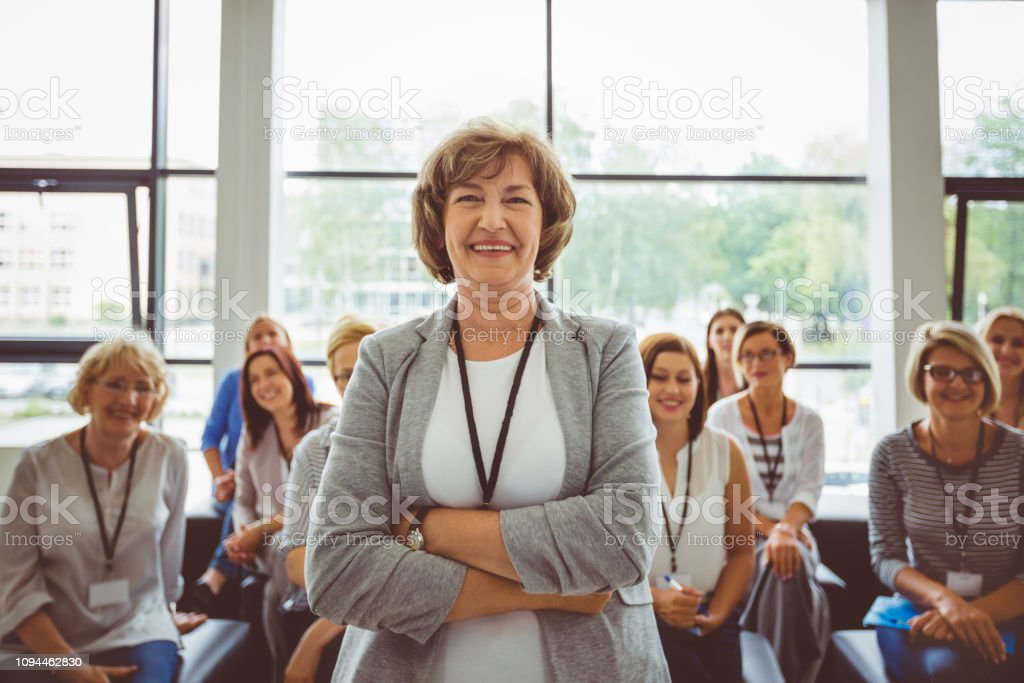 Smiling mature female speaker at seminar Portrait of smiling mature female speaker in seminar hall with audience in background Adult Stock Photo