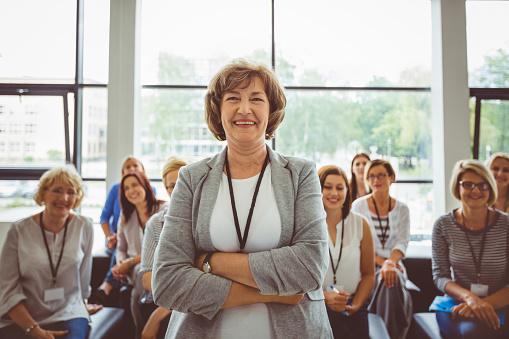Smiling Mature Female Speaker At Seminar Stock Photo - Download Image Now