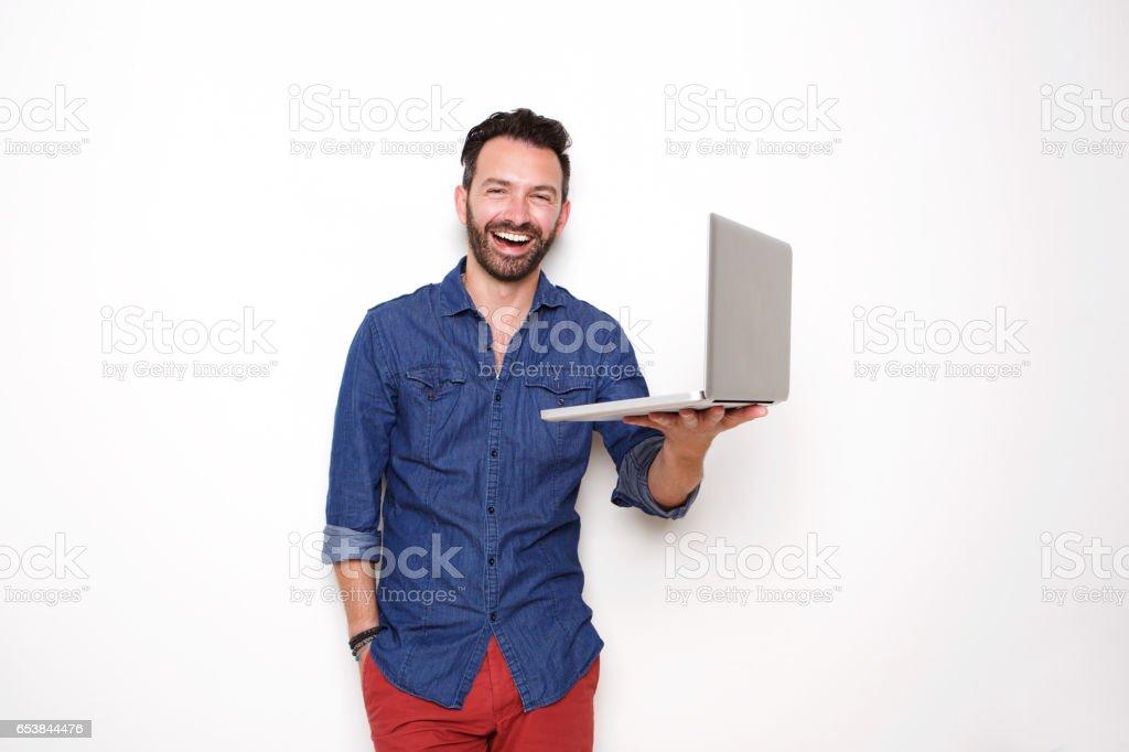 Smiling mature guy holding laptop stock photo