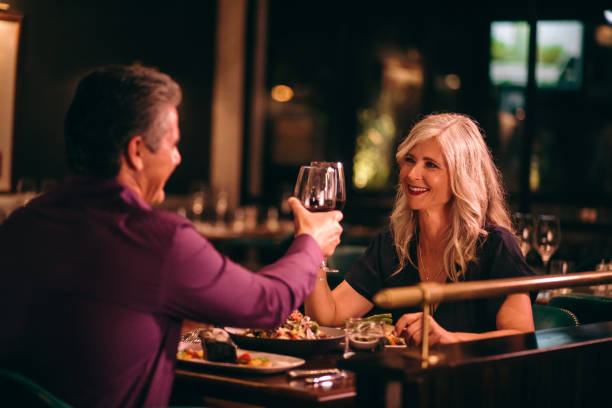 smiling mature husband and wife toasting with wine at dinner - date night stock pictures, royalty-free photos & images