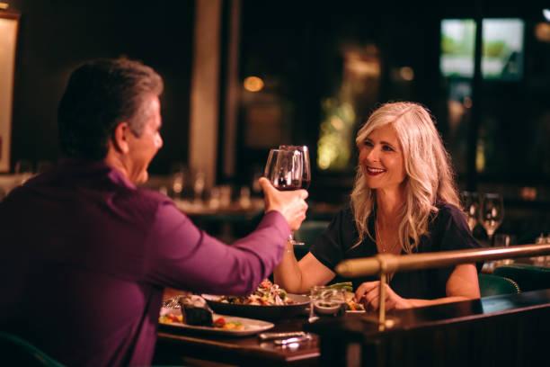 sonriente marido maduro y mujer brindando con vino en la cena - date night fotografías e imágenes de stock