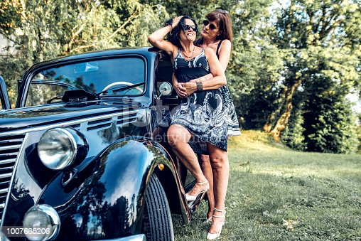 Smiling Mature Lesbian Couple By Their Vintage Gangster Car.
