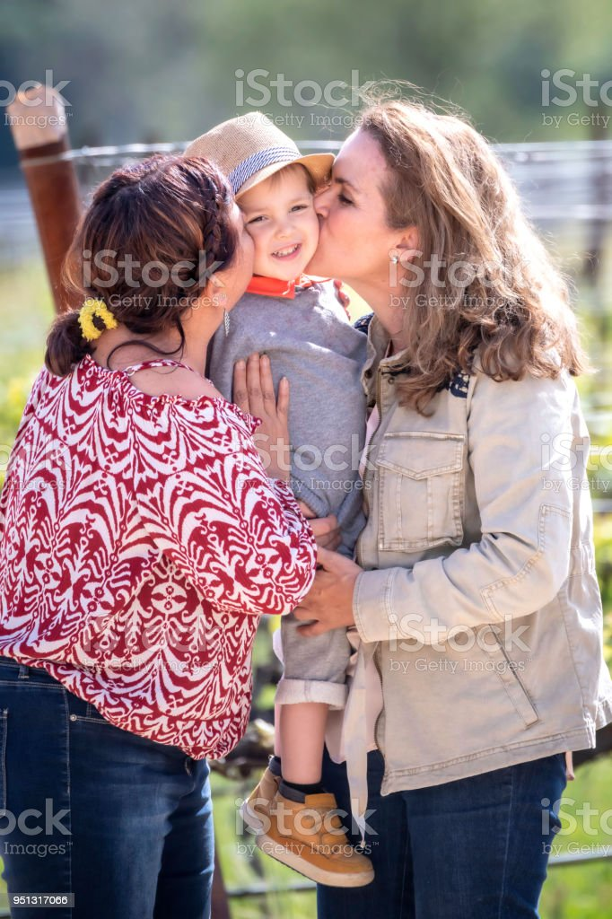 Smiling Mature Lesbian Couple Posing With Their Son Stock Image