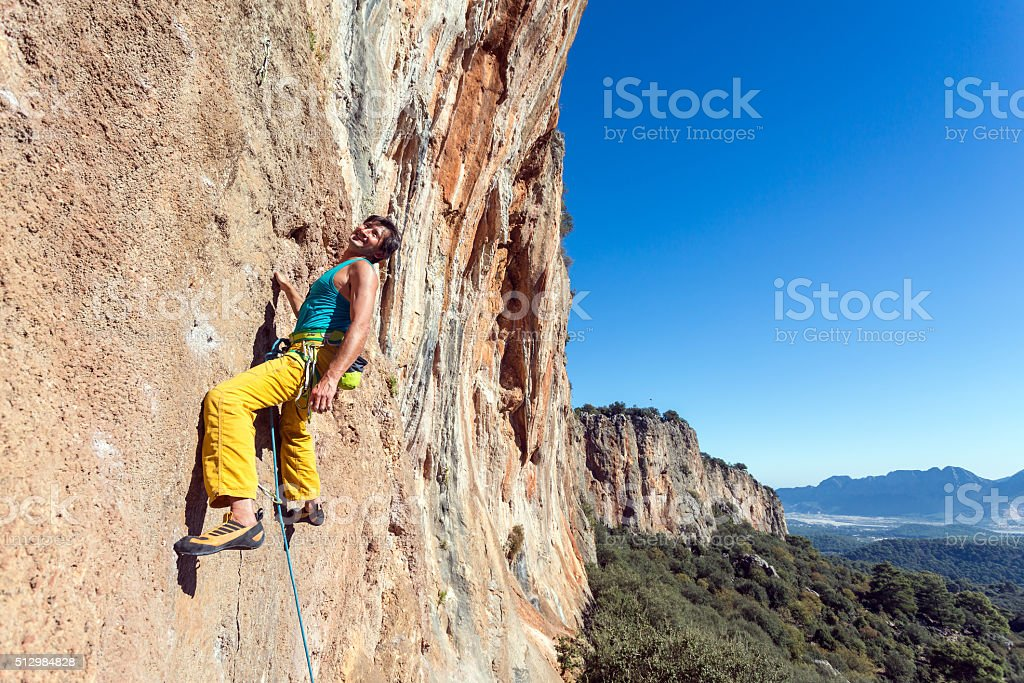 Smiling mature male extreme Climber hanging on rocky wall easy - Stock  image .