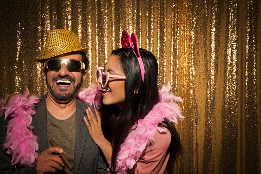 Smiling mature man and young woman enjoying with props at party.