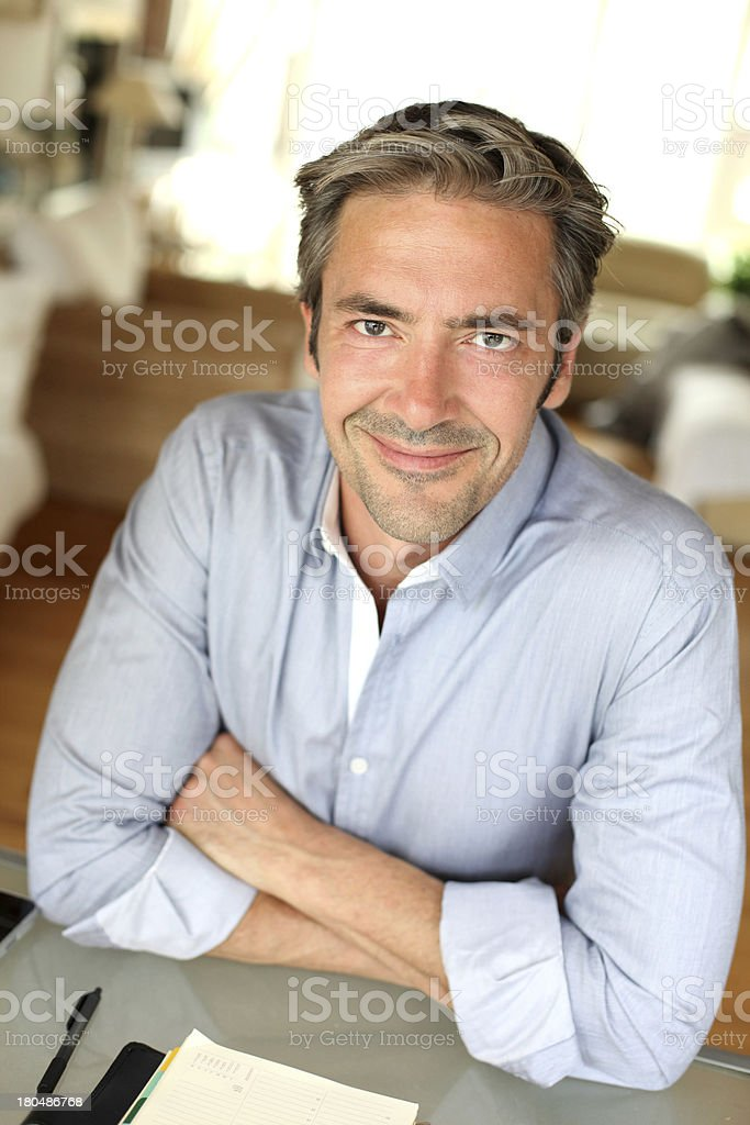 Smiling mature man at home with arms crossed royalty-free stock photo
