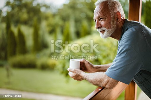 Senior man having his morning coffee on a balcony and day dreaming. Copy space.