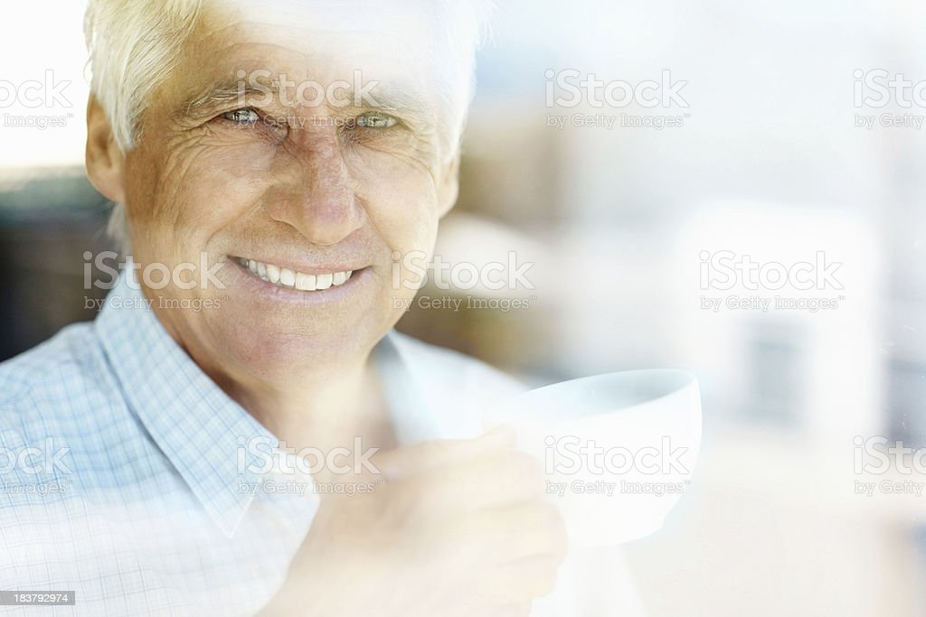 Smiling, mature man having a cup of coffee royalty-free stock photo