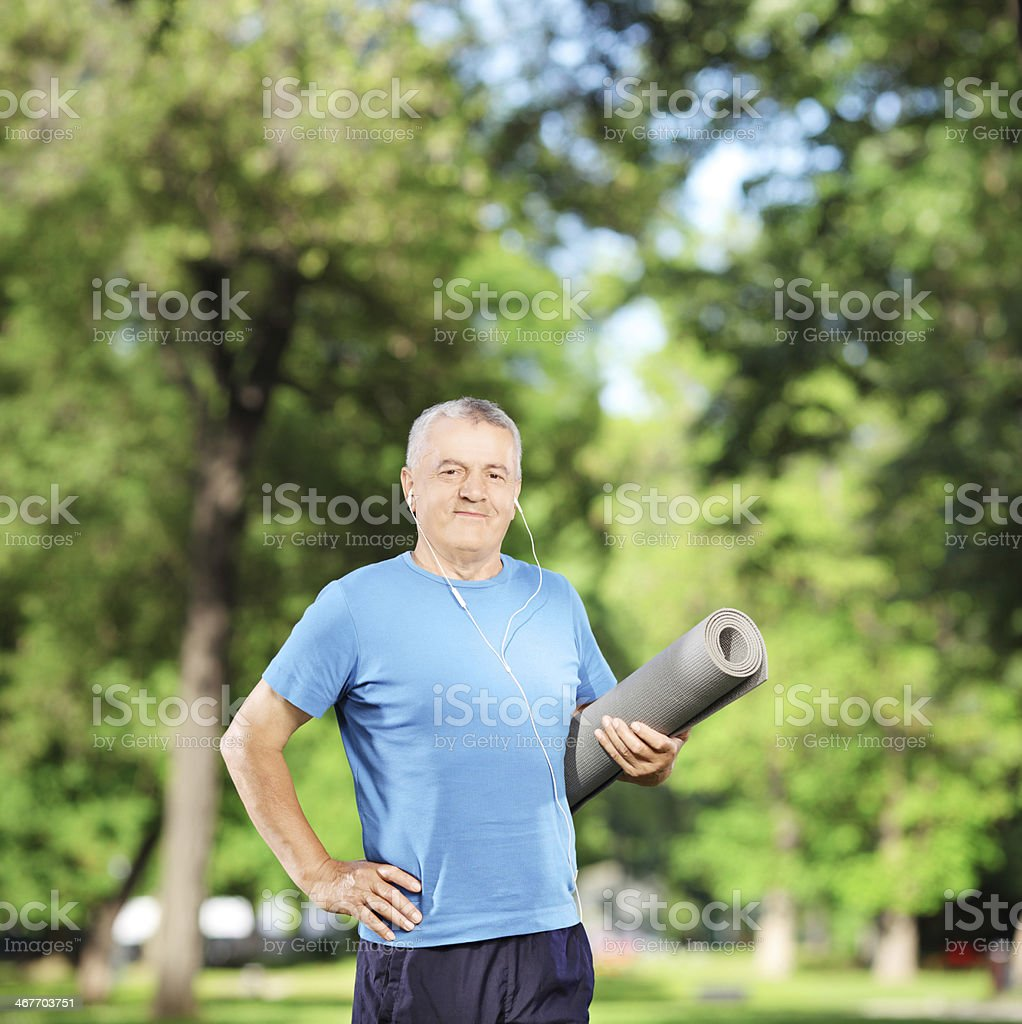 Smiling mature man holding a mat in park stock photo
