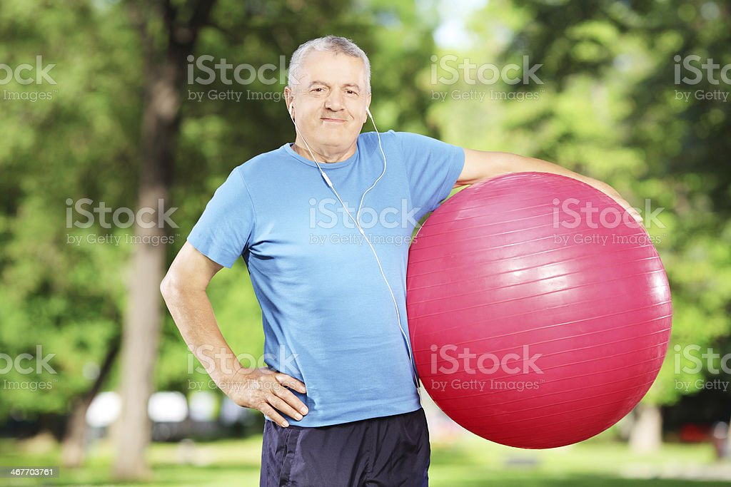 Smiling mature man holding a pilates ball in park stock photo