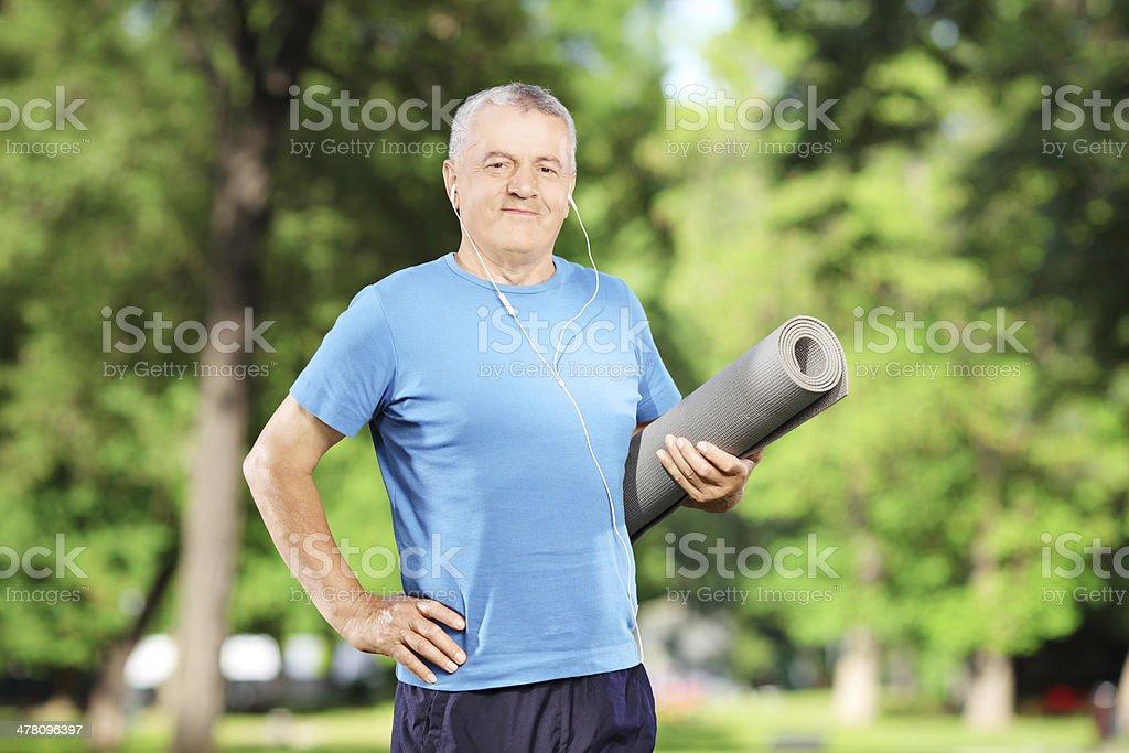 Smiling mature man holding an exercising mat in park stock photo
