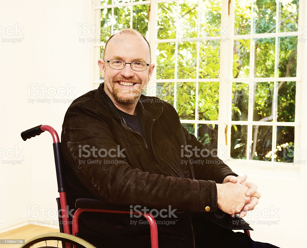 Smiling mature man in wheelchair looks contented stock photo