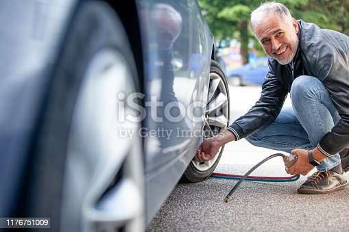 Smiling Mature Man Inflating Car Tires Outdoors.