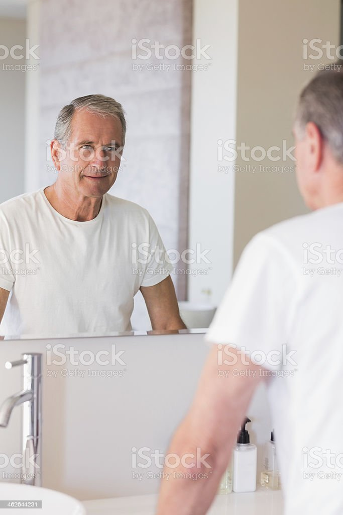 Smiling mature man looking at his reflection in mirror royalty-free stock photo