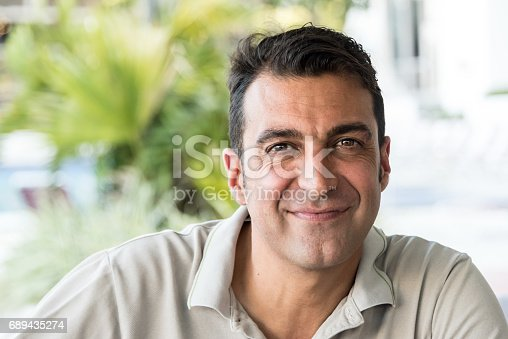 Smiling middle eastern or hispanic mature man looking at the camera