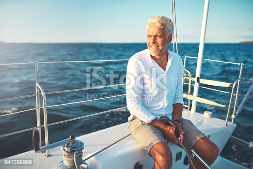 Mature man sitting on the deck of his boat enjoying a sunny day sailing on the open ocean