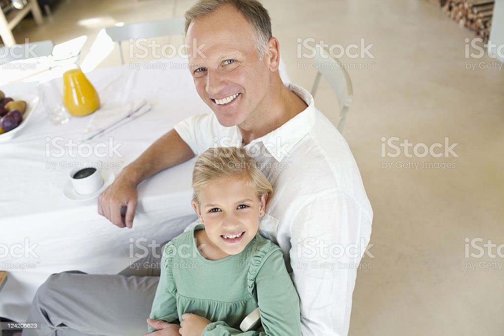 Smiling mature man with his daughter over breakfast table royalty-free stock photo