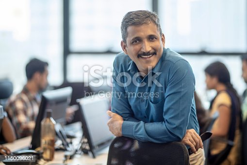 Portrait of smiling mature manager leaning on chair. Confident male entrepreneur is at creative office. He is in formalwear.