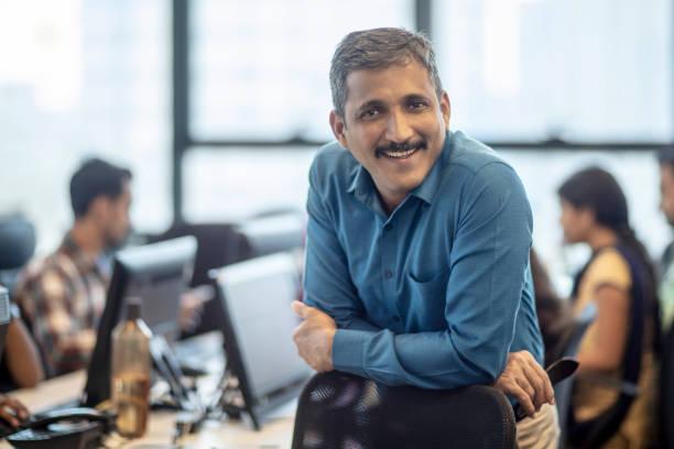Lächelnde, reife Managerin sitzt im Kreativbüro – Foto