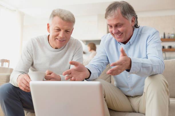 Smiling mature men using laptop while sitting at home stock photo
