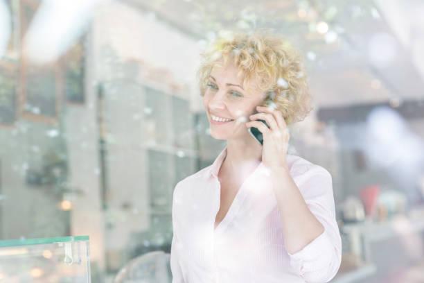 Smiling mature owner talking on smartphone seen through restaurant window stock photo